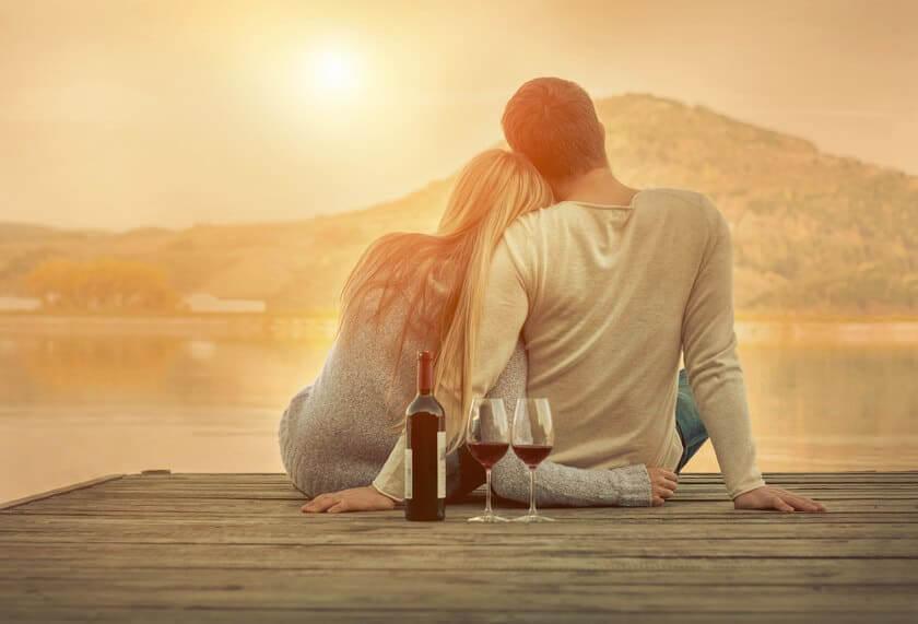 Paar sitzt im Sonnenuntergang mit Rotweinflasch und Rotweingläsern