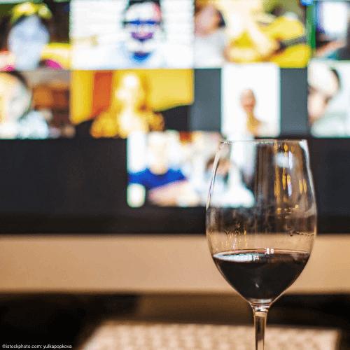 Mit Rotwein befülltes Weinglas vor Bildschirm mit vielen Videochat-Fenstern